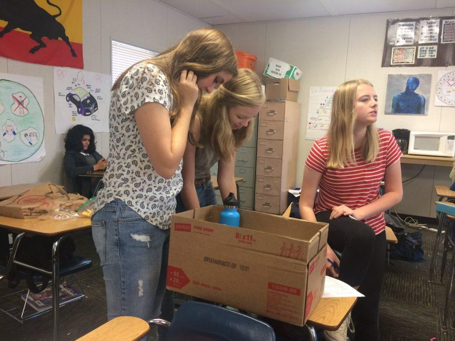Sophomores Lucy Ryall, Linnea Erisman and Sylvia Young of Spanish teacher David Bairs homeroom add newly found objects to their scavenger hunt box.