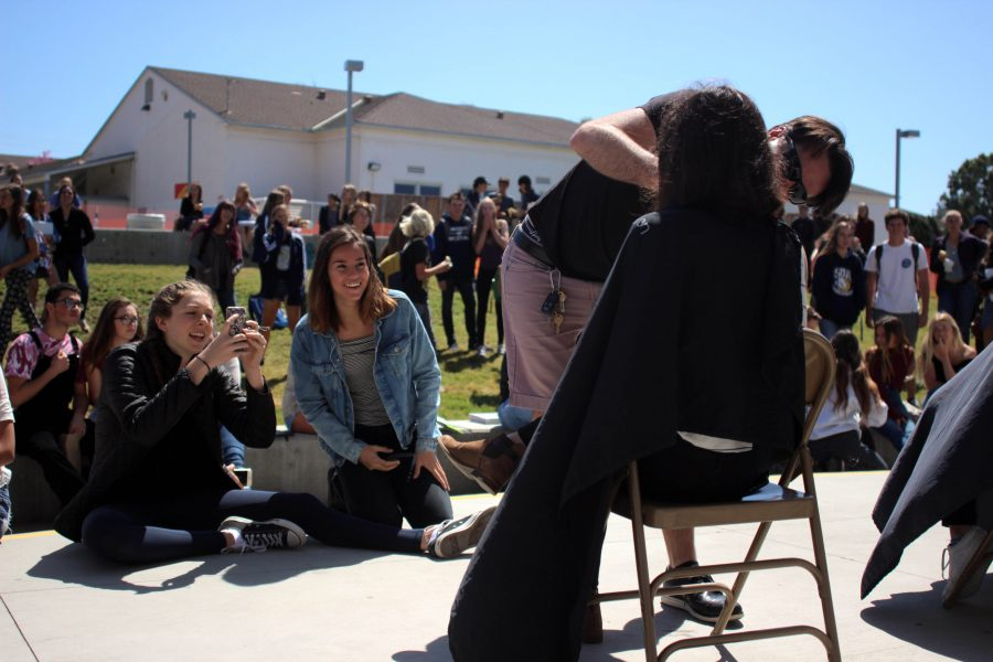 Students+excitedly+watch+as+others+get+their+hair+cut+in+front+of+the+PAC.