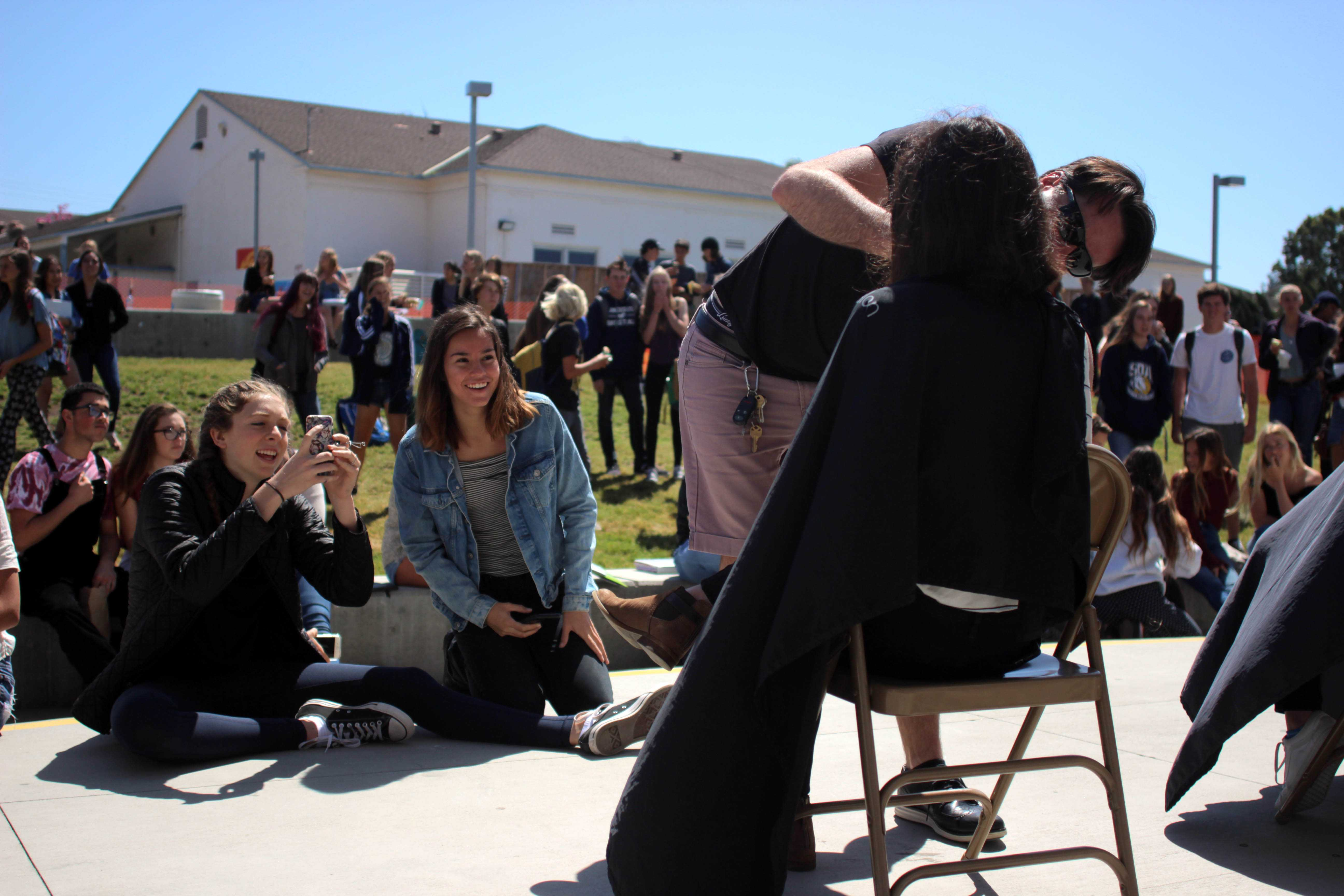 Students excitedly watch as others get their hair cut in front of the PAC.