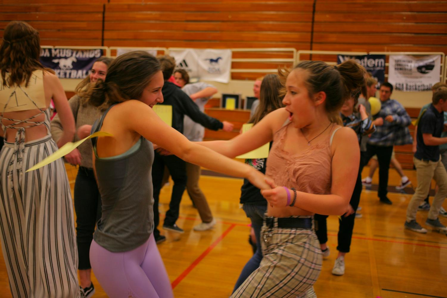 Juniors Adriana Billante and Kiomi Yamada jam to the music during last week's homeroom dance party.