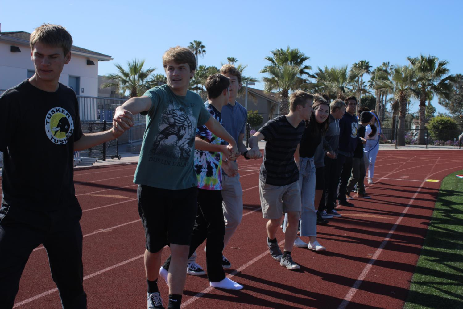 Students link arms as part of the relay race event.