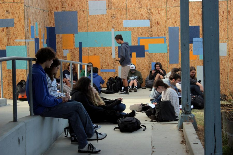Students sit outside their homeroom class while waiting for doors to be unlocked.