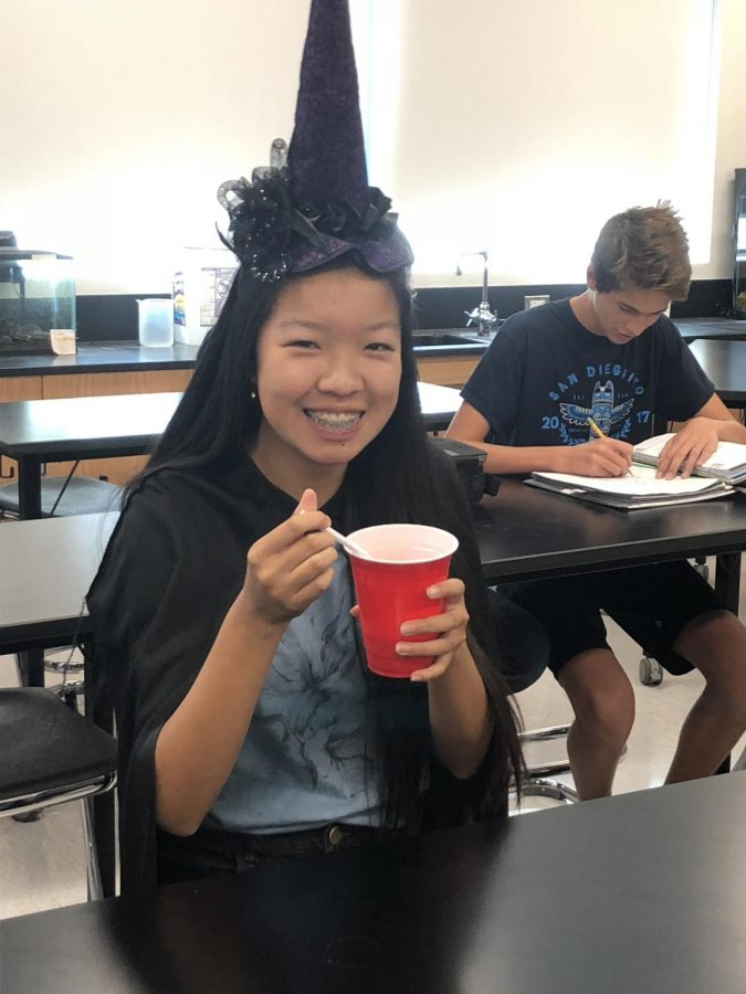 Sophomore Emily Liang holding her butter beverage while wearing a witch outfit.