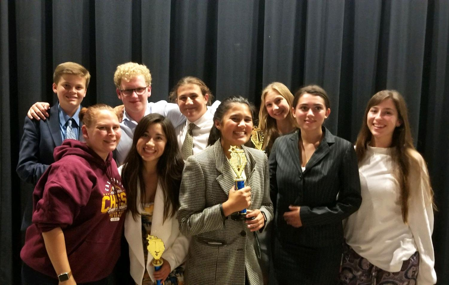 Speech and Debate team members and teacher Lily Bolig stand proudly with their trophies after last weekend's tournament.