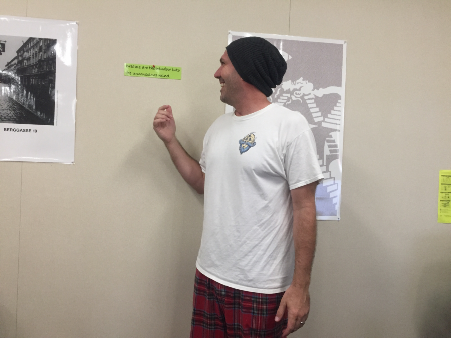 AP Psychology teacher, James Hrzina, shows off his pajamas in front of a quote about dreams by Sigmund Freud.