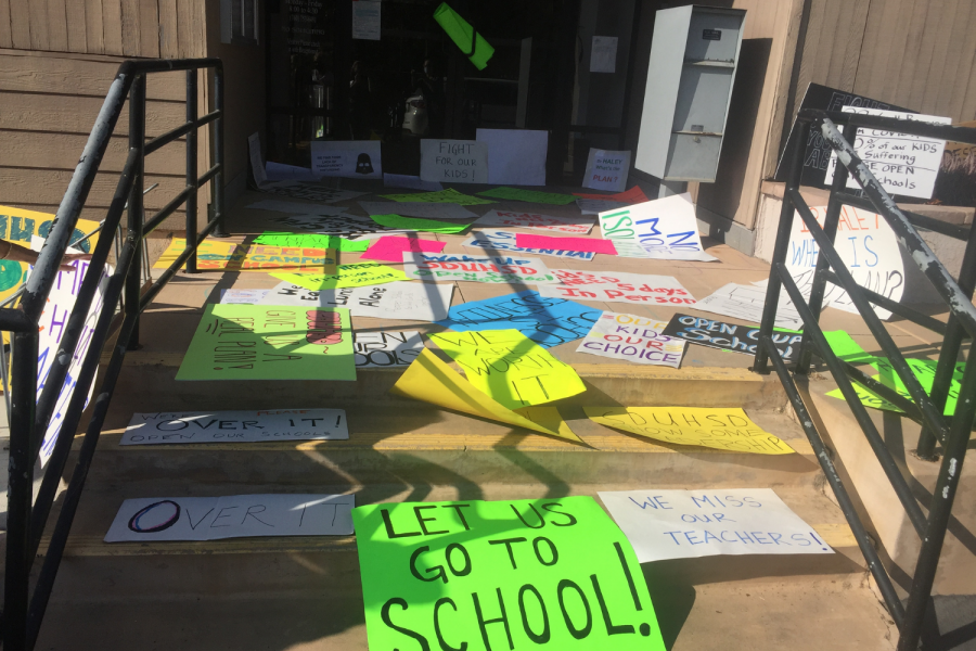 People leave signs in front of the district office with messages like 'Let us go to school!'