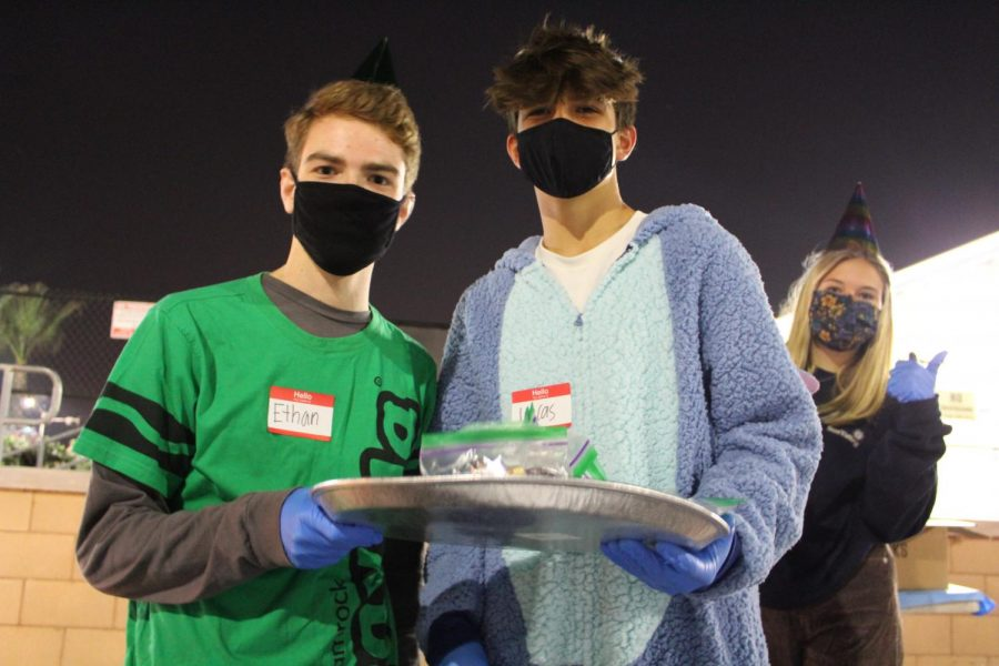 Juniors Ethan Fitzgerald (left) Lucas Casazza (middle) and sophomore Maisie Leeuw (right) pass out candy bags in the front parking lot for students to enjoy