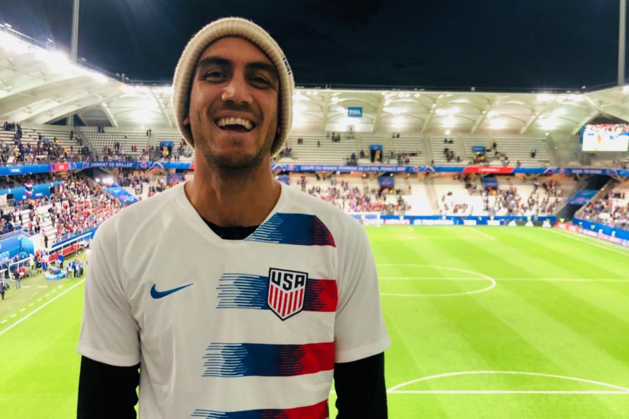 Mr. Ramirez poses in front of a soccer stadium rooting for USA