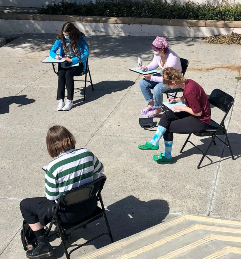Four girls sitting in a school chair desk writing