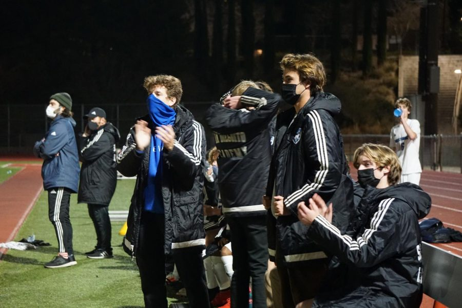 three boys watching the soccer game in a stadium with a blue mask and black masks