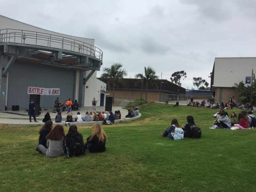 students sitting on the grass while watching in the pac