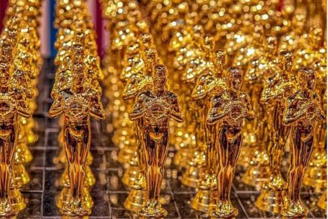 Image of many golden Oscars awards lined up together.