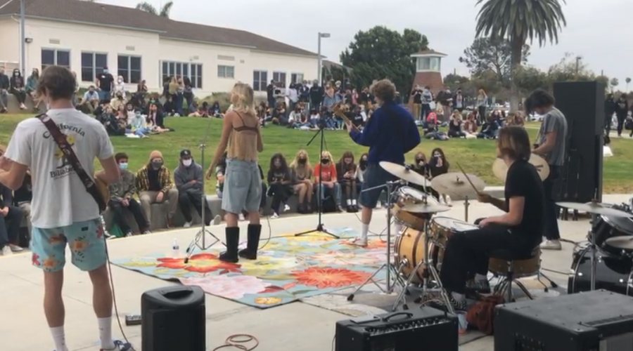 four band performers with crowd in front